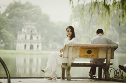 Couple Sitting Apart on a Bench, While the Woman Looks Out in the Distance
